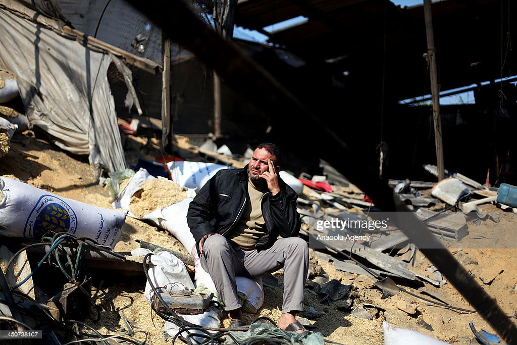 A Palestinian man sits and looks at the damage in a chicken farm after it was hit by an Israeli air strike in Khan Yunis in the southern Gaza Strip on November 20, 2013.