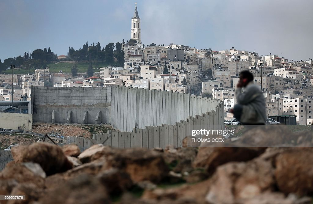 Palestinian man sits near Israel's controversial separation barrier dividing the Palestinian neighbourhood of AlTur in the Israeli annexed East...