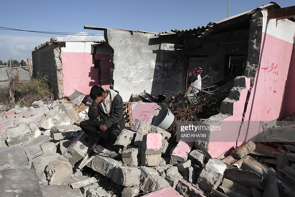 A Palestinian man sits on the rubble of his home following an Israeli military air strike in Rafah town in the southern Gaza Strip, on November 11, 2012. The flare-up which began November 10, was one of the most serious since Israel's devastating 22-day operation in the Gaza Strip over New Year 2009, has culminated in six Palestinians being killed and 32 injured by Israeli strikes after militants fired on an Israeli jeep, wounding four soldiers, medics and witnesses said. AFP PHOTO/ SAID KHATIB