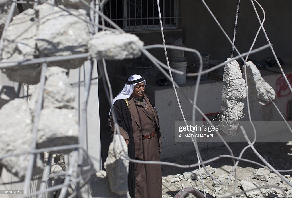 A Palestinian man stands amidst the rubble of his house after a bulldozer hired by the Jerusalem municipality destroyed the building in the Israeli annexed East Jerusalem neighbourhood of al-Tur on April 24, 2013. Palestinian homes built without a construction permit are often demolished by order of the Jerusalem municipality.