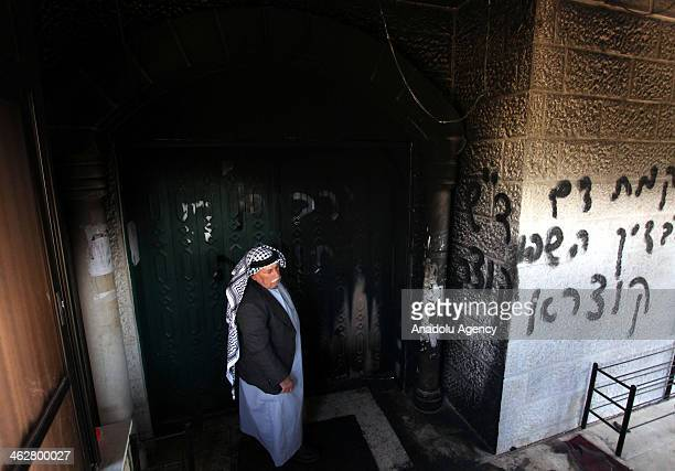 Palestinian man stands in the entrance to of the Ali Ibn Abi Talib mosque which is set fire by Jewish settlers caused partial damage to the worship...