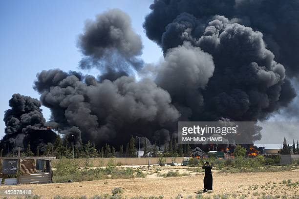 A Palestinian man stands looking as flames engulf the fuel tanks of the only power plant supplying electricity to the Gaza Strip after it was hit by...