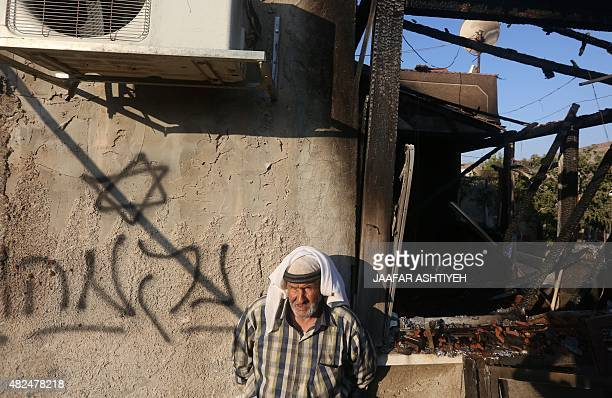 A Palestinian man stands next to a graffiti reading in Hebrew 'Revenge' as he looks at the damage after a house was set on fire by Jewish settlers in...