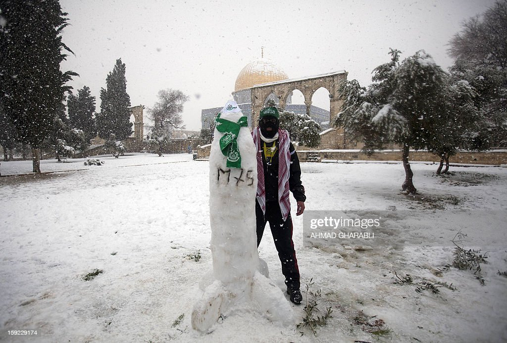 A Palestinian man stands next to a snow sculpture in the shape of an M75 long-range Hamas rocket at the Al-Aqsa mosque compound in the old city of Jerusalem on January 10, 2013. Jerusalem was transformed into a winter wonderland after heavy overnight snowfall turned the Holy City and much of the region white, bringing hordes of excited children onto the streets. AFP PHOTO/AHMAD GHARABLI