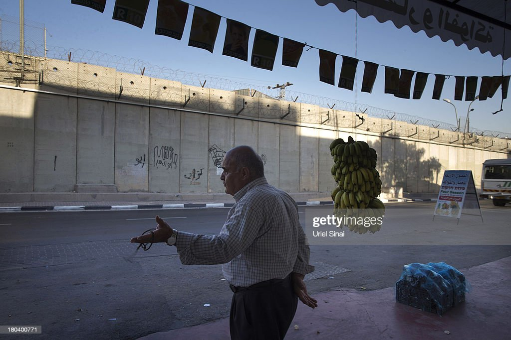 A Palestinian man stands outside his shop along the Israeli West Bank barrier on the outskirts of Jerusalem on September 12, 2013 in Aram, West Bank. The twenty-year anniversary of the Oslo Accord, which was to set up a framework for peace between Israel and Palestine, will be marked on September 13.