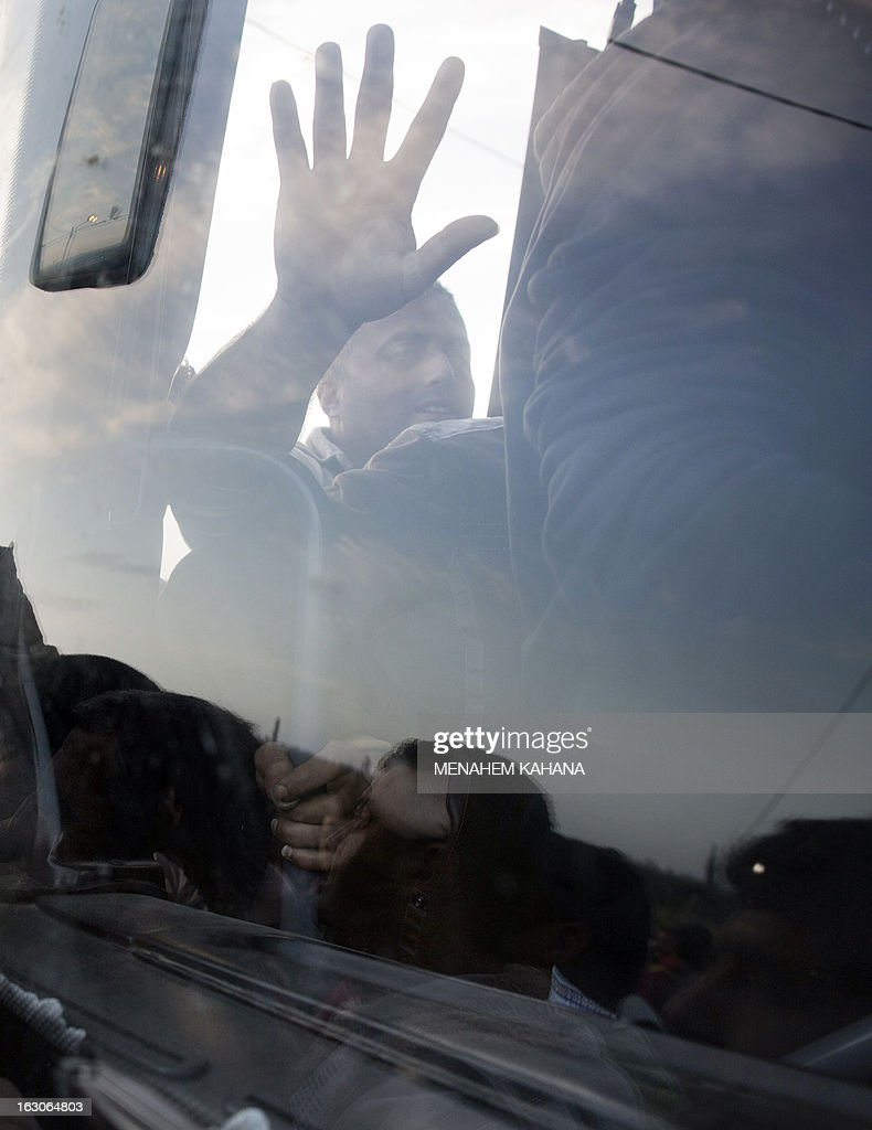 A Palestinian man supports himself on the windscreen of a bus as he and other push to board the new bus line made available by Israel to take Palestinian labourers from the Israeli army crossing Eyal, near the West Bank town of Qalqilya, into the Israeli city Tel Aviv, on March 4, 2013.Thousands of Palestinians enter Israel to work every day after receiving permits, many of them in private vans. The new line will not be available for Jewish settlers.