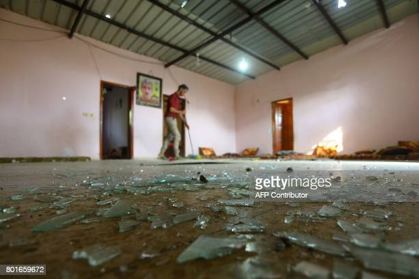 Palestinian man sweeps shattered glass inside his house following an Israeli air strike in Gaza City on June 27 2017 Israeli airstrikes hit a series...