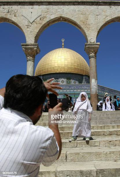 A Palestinian man takes pictures of his daughter at the AlAqsa mosque compound in Jerusalem's old city during the third Friday prayers of Ramadan on...