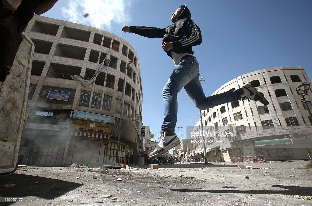 A Palestinian man throws a stone towards Israeli security during clashes in the West Bank city of Hebron following the death of a Palestinian prisoner on April 2, 2013. The Palestinian leadership blamed Israel for the death of Maisara Abu Hamdiyeh, a long-term prisoner with cancer, hiking tensions over a tinderbox issue closely followed on the Palestinian street.