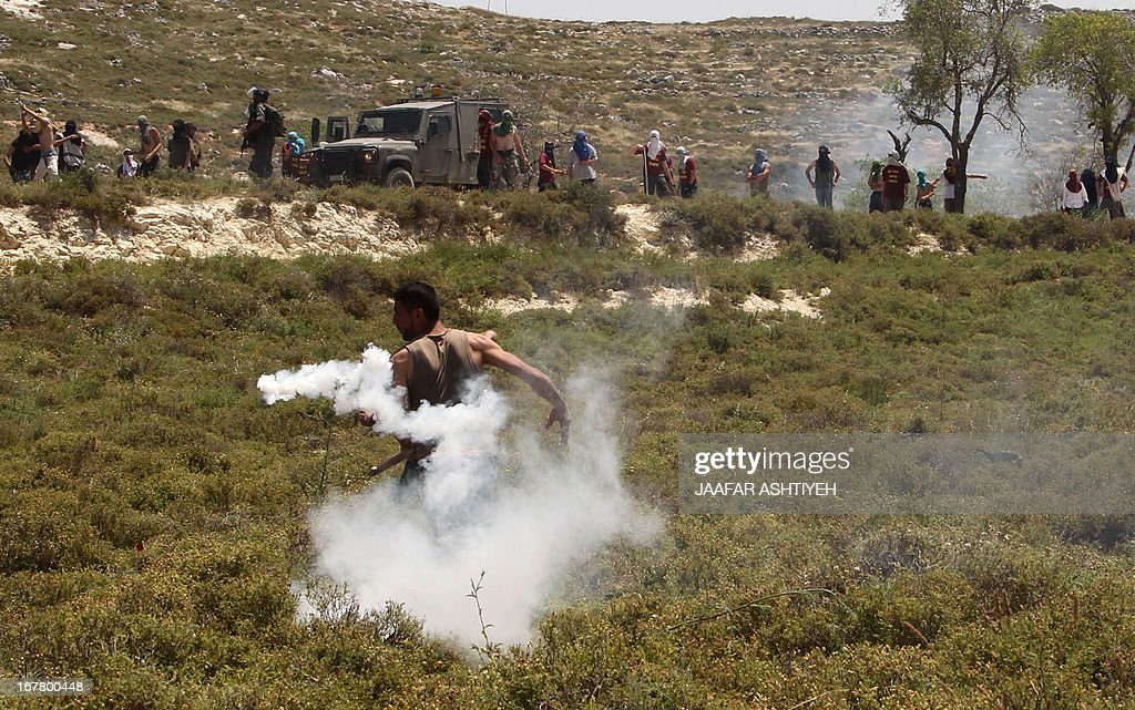 A Palestinian man throws back a tear gas canister towards masked Israeli settlers and members of the Israeli security forces during clashes in the West Bank village of Urif, near Nablus, on April 30, 2013 after an Israeli settler was stabbed to death by a Palestinian man in the northern West Bank. An Israeli settler was stabbed to death by a knife-wielding Palestinian near Tapuah junction south of Nablus, in the first fatal anti-Israeli attack in the territory in 18 months, officials said. AFP PHOTO/JAAFAR ASHTIYEH