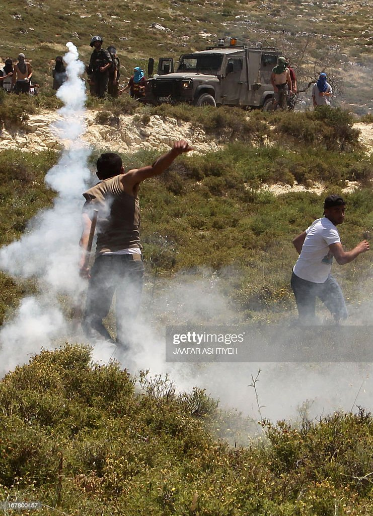 A Palestinian man throws back a tear gas canister towards masked Israeli settlers and members of the Israeli security forces during clashes in the West Bank village of Urif, near Nablus, on April 30, 2013 after an Israeli settler was stabbed to death by a Palestinian man in the northern West Bank. An Israeli settler was stabbed to death by a knife-wielding Palestinian near Tapuah junction south of Nablus, in the first fatal anti-Israeli attack in the territory in 18 months, officials said.