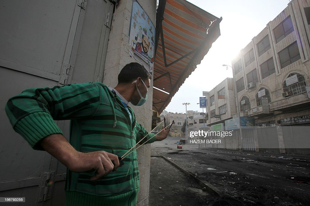 A Palestinian man uses a slingshot to lob a stone towards Israeli border police in the West Bank city of Hebron on November 21, 2012, following protests against the ongoing Israeli military offensive on the Gaza Strip. Israel launched its offensive on November 14 with the targeted killing of a Hamas military chief. Since then, 147 Palestinians and five Israelis have been killed. AFP PHOTO/HAZEM BADER