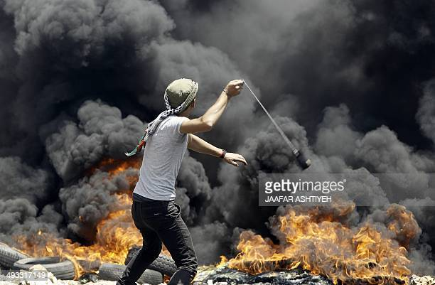 A Palestinian man uses a slingshot to throw stones during clashes with Israeli security forces following a weekly protest against the expropriation...