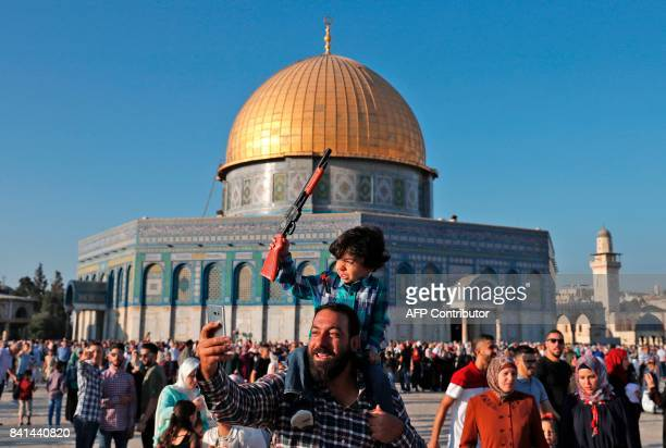 A Palestinian man uses his cell phone to take a 'selfie' photograph as he carries a child holding a toy plastic rifle while celebrating on the first...