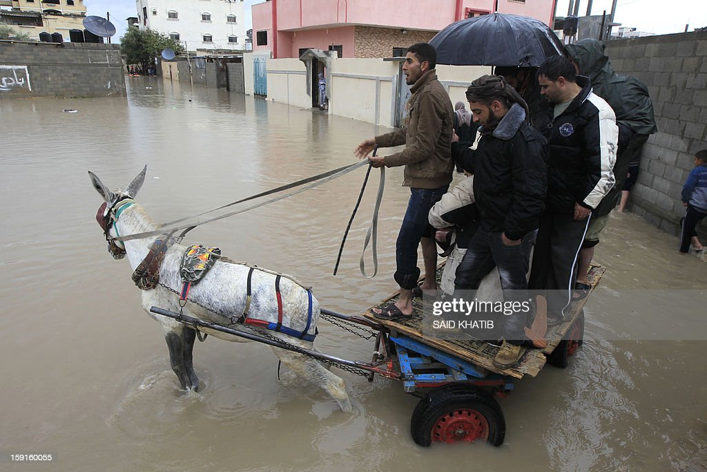 A Palestinian man uses his donkey cart to transport people across a flooded street in the Rafah refugee camp, in the southern Gaza Strip, on January 9, 2013. A storm has hit the eastern Mediterranean coast and heavy rains with flooding are forecast in Israel and the Palestinian territories for the next couple of days, with a good chance of snow falling in the higher elevations. AFP PHOTO / SAID KHATIB