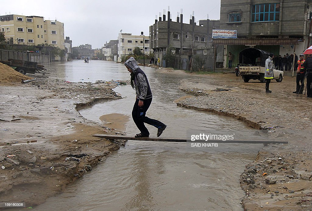 A Palestinian man walks along a plank, as flood waters sweep down along a street, in the Rafah refugee camp, in the southern Gaza Strip, on January 9, 2013. A storm has hit the eastern Mediterranean coast and heavy rains with flooding are forecast in Israel and the Palestinian territories for the next couple of days, with a good chance of snow falling in the higher elevations.