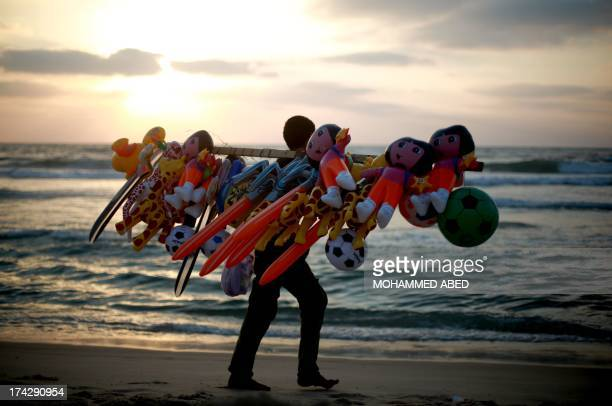 A Palestinian man walks along the beach selling balloons as the sun sets over the Gaza Strip on July 23 ending a day of fasting during the holy...