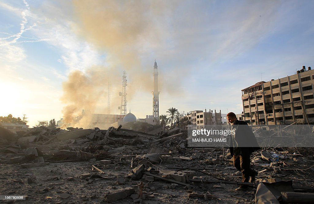 A Palestinian man walks amidst debris at the destroyed compound of the internal security ministry in Gaza City after it was targeted by an Israeli air strike overnight on November 21, 2012. Fighting raged on both sides of Gaza's borders Wednesday despite intensified efforts across the region to thrash out a truce to end a week of violence that has cost 136 Palestinian and five Israeli lives. AFP PHOTO/MAHMUD HAMS