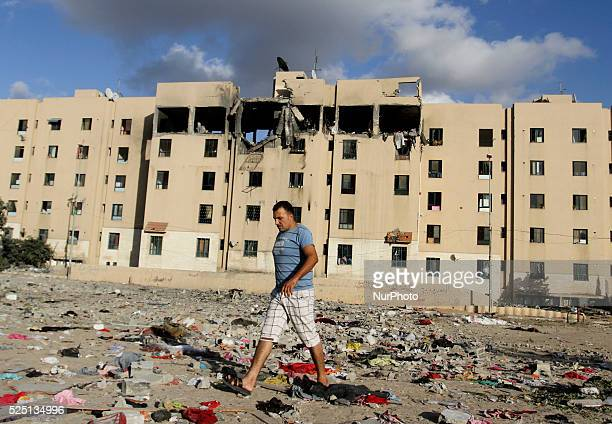 A Palestinian man walks between clothes and rubble scattered on the ground in front of a destroyed house following an Israeli airstrike in Beit...