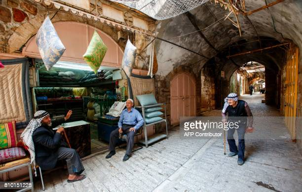 A Palestinian man walks by another two sitting outside a cushion shop in the old market of the divided West Bank city of Hebron on July 7 2017 On...