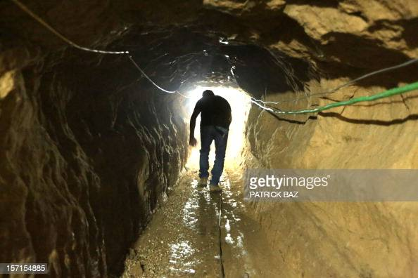 A Palestinian man walks from the Egyptian side of the border in a repaired bombed smuggling tunnel linking the Gaza Strip to Egypt in Rafah on...