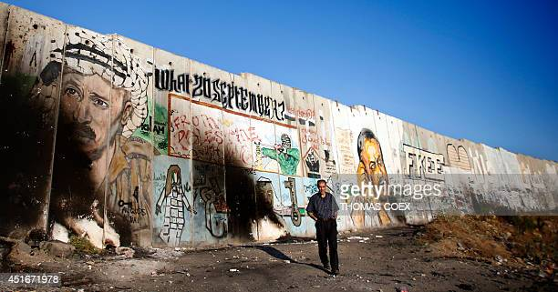 A Palestinian man walks in front of a section of the Israeli separation barrier breaing a mural of late Palestinian leader Yasser Arafat and jailed...