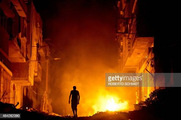 A Palestinian man walks past a fire in a street set by a home owner in an effort to keep mosquitoes away from their shattered homes in Shejaiya on...