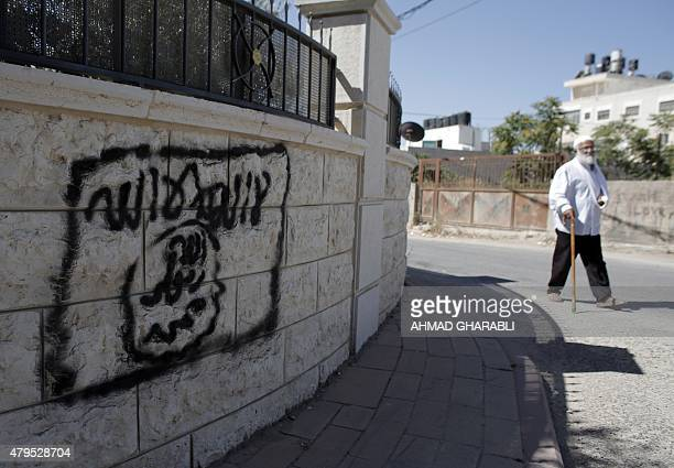 A Palestinian man walks past a graffiti portraying the Islamic State group's flag in the East Jerusalem neighbourhood of Beit Hanina on July 5 2015...
