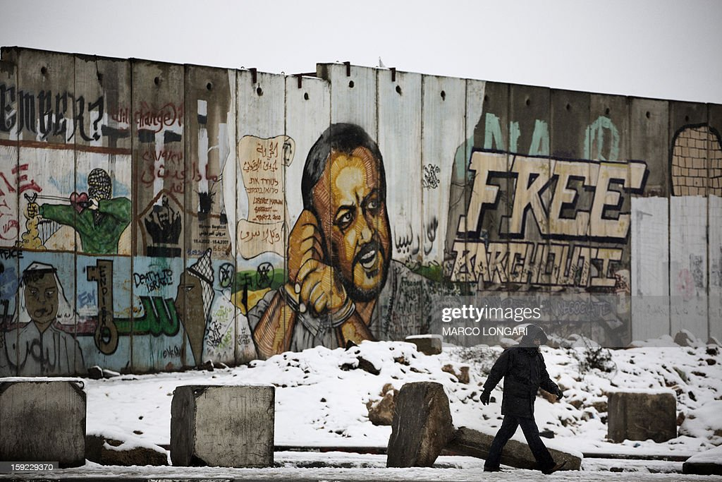 A Palestinian man walks past a graffiti-covered section of the controversial Israeli separation wall at the Qalandia checkpoint in the Israeli occupied West Bank on January 10, 2013. The worst storms in a decade left swathes of Israel and Jordan under a blanket of snow and parts of Lebanon blacked out, bringing misery to a region accustomed to temperate climates. AFP PHOTO/MARCO LONGARI