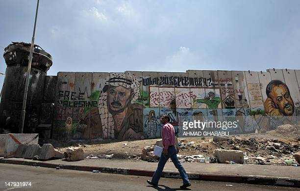 A Palestinian man walks past a mural of late Palestinian leader Yasser Arafat and jailed Fatah leader Marwan Barghuti on a section of Israel's...