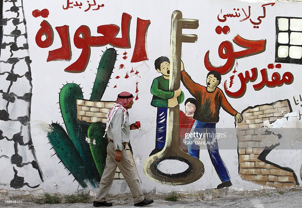 A Palestinian man walks past a mural on a wall in the West Bank city of Jenin reading in Arabic: 'So that we don't forget the sacred right to return' on May 13, 2013, as Palestinians and Arab Israelis prepare to mark Nakba day, which commemorates the exodus of hundreds of thousands of their kin after the establishment of Israel state in 1948.