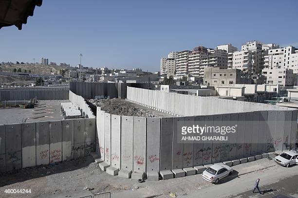 A Palestinian man walks past a new section of Israel's controversial separation barrier in the Shuafat refugee camp in east Jerusalem on December 6...
