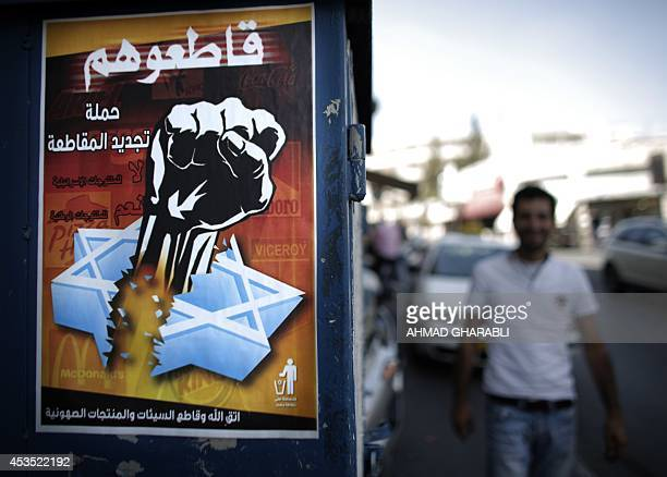 A Palestinian man walks past a poster calling people to boycott Israeli goods following the latest war between Hamas militants in the Gaza Strip and...