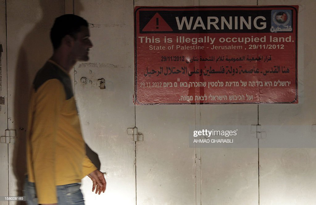 A Palestinian man walks past a sign put up on iron doors urging Jewish settlers to leave from the 'State of Palestine' in the mostly Arab east Jerusalem neighborhood of Atur on December 9, 2012
