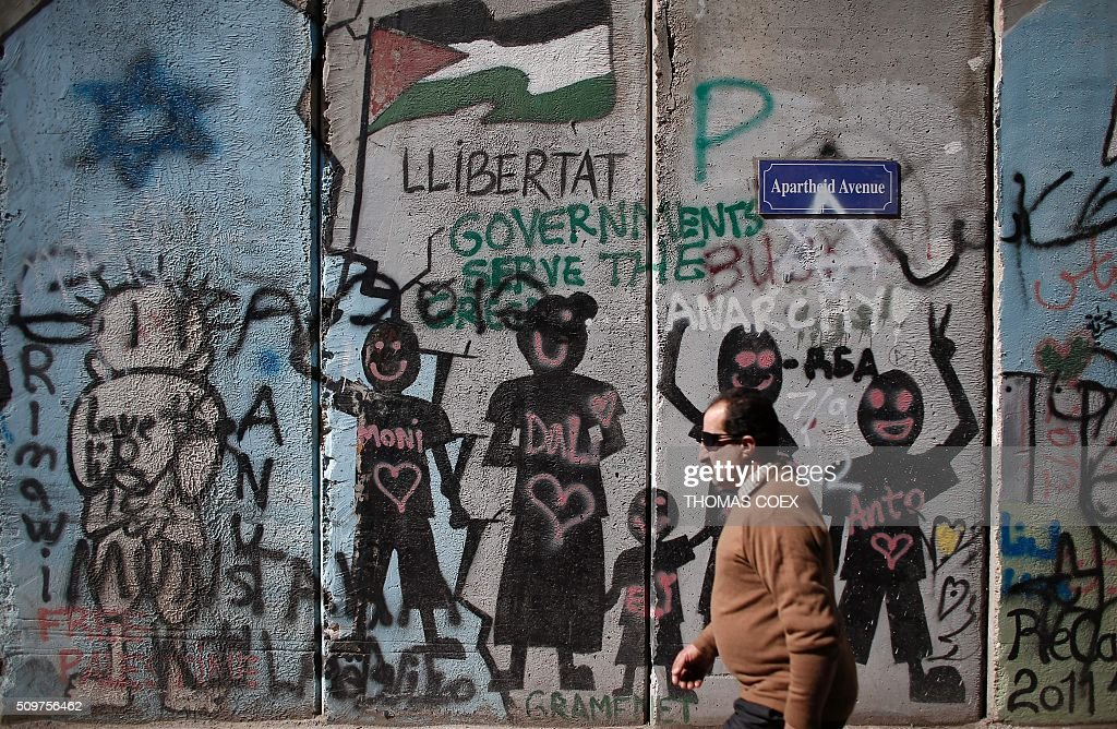 A Palestinian man walks past graffiti painted on Israel's controversial separation barrier in the West Bank town of Bethlehem, on February 12, 2016. / AFP / THOMAS COEX