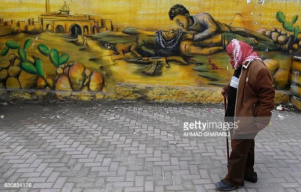 Palestinian man walks past graffiti sprayed on a wall in the West Bank refugee camp of Qalandia on January 3 2017 / AFP / AHMAD GHARABLI