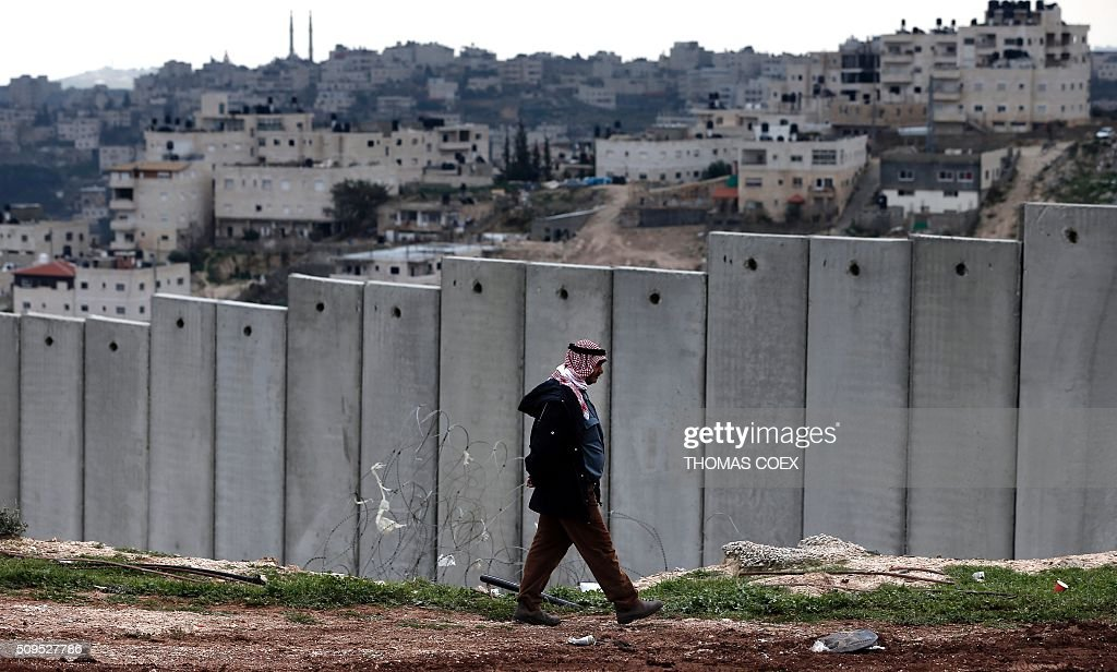 A Palestinian man walks past Israel's controversial separation barrier the Palestinian neighbourhood of Al-Tur in the Israeli annexed East Jerusalem with the West Bank, on February 11, 2016. / AFP / THOMAS COEX