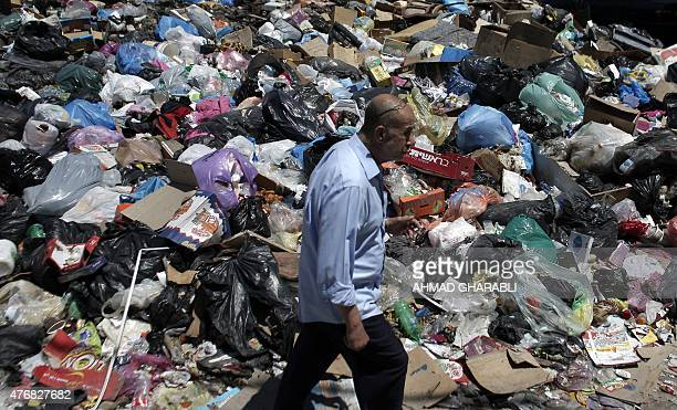 A Palestinian man walks past piles of accumulated rubbish in the Palestinian refugee camp of Shuafat in east Jerusalem on June 12 2015 The refugee...