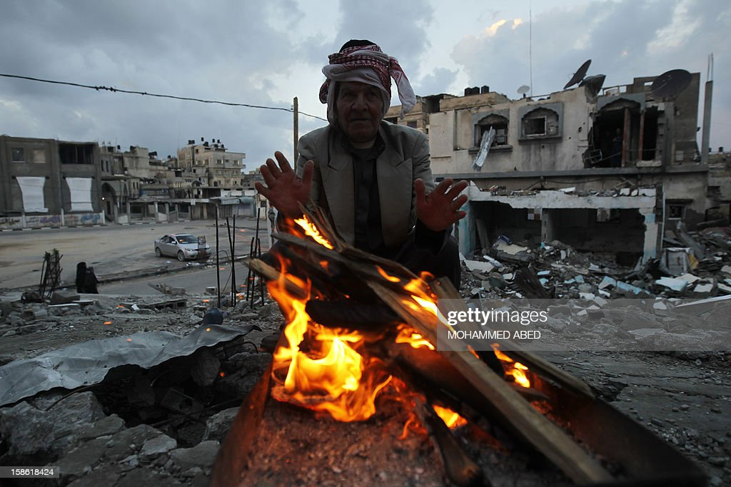 A Palestinian man warms himself by a fire next to houses which were destroyed during November's eight-day confrontation between Israel and Gaza militants, on December 21, 2012 in Beit Lahia, northern Gaza Strip. The eight-day confrontation claimed the lives of 177 Palestinians, mostly civilians, and six Israelis, medical sources on both sides said.