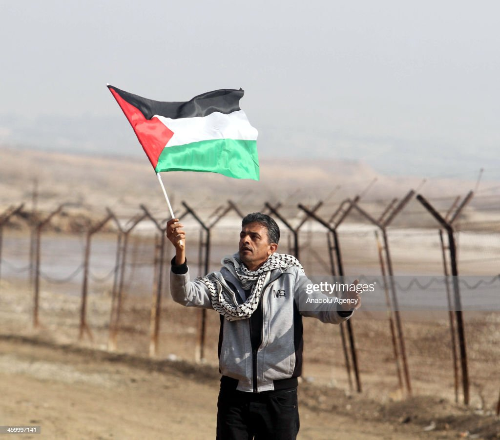 A Palestinian man waves national flag during a protest against the Israel's intention to annex the Jordan Valley, near the West Bank City of Jericho on January 01, 2013.