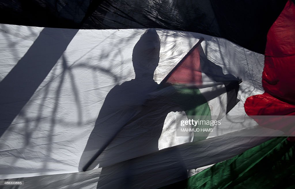A Palestinian man waves the national flag during a demonstration demanding the trial of Israeli Prime Minister Benjamin Netanyahu and former prime minister Ehud Barak for war crimes, in front of the United Nations headquarters in Gaza city on February 10, 2914.