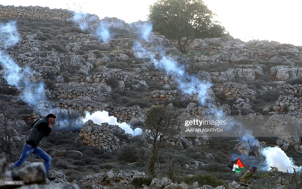 A Palestinian man waving his national flag and a fellow protestor run for cover from tear gas canisters fired by Israeli soldiers during clashes after Israeli settlers attacked villagers in the northern West Bank village of Qusra on November 24, 2012. PHOTO