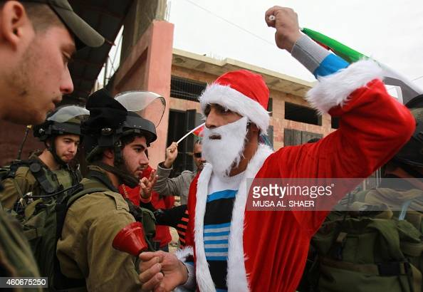 A Palestinian man wearing a Santa Claus costume and waving the national flag is confronted by Israeli soldiers during a weekly demonstration on...