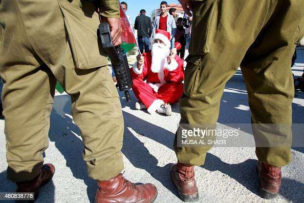A Palestinian man wearing a Santa Claus costume and waving the national flag sits on the ground infront of Israeli soldiers during a weekly...
