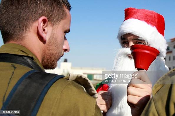 A Palestinian man wearing a Santa Claus costume and waving the national flag is confronted by an Israeli soldier during a weekly demonstration on...