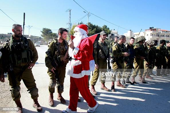 A Palestinian man wearing a Santa Claus costume and waving the national flag rings his bell as he walks by Israeli soldiers during a weekly...