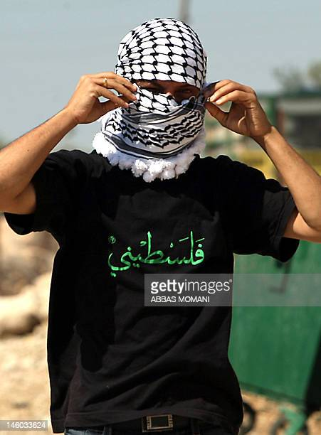 A Palestinian man wearing a Tshirt with the logo in Arabic that reads 'Palestine' covers his nose from tear gas fired by Israeli soldiers during a...