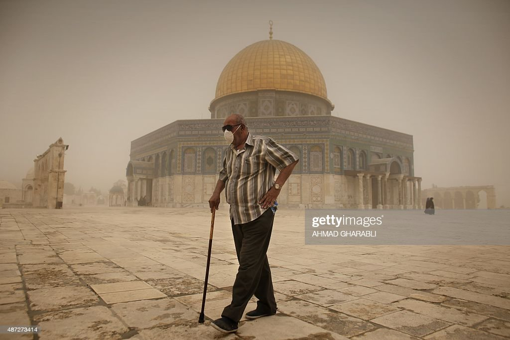 A Palestinian man wears a mask to protect his face from the dust as he walks past the Dome of the Rock mosque in the alAqsa Mosque compound during a...