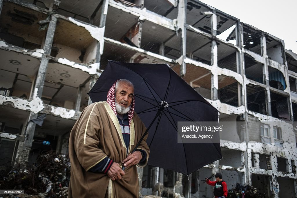 Palestinian man, whose home has been destroyed by Israeli assaults, protects himself with an umbrella during heavy rain, in Gaza City, Gaza on February 7, 2016.