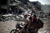 Palestinian man with his children rides on a bike through the debris as Palestinians inspect and collect remains from the rubble of a destroyed...